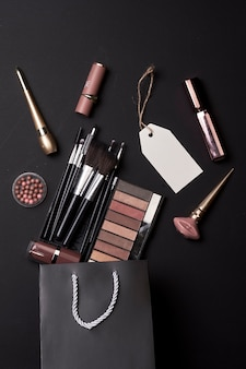 Black friday concept various cosmetic items in black shopping bag