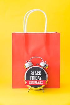 Concetto di venerdì nero con allarme davanti a borsa rossa