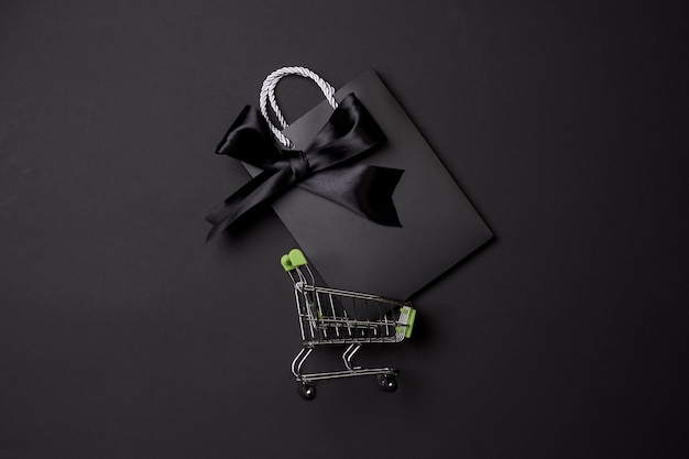 Black friday concept with shopping trolley on black background