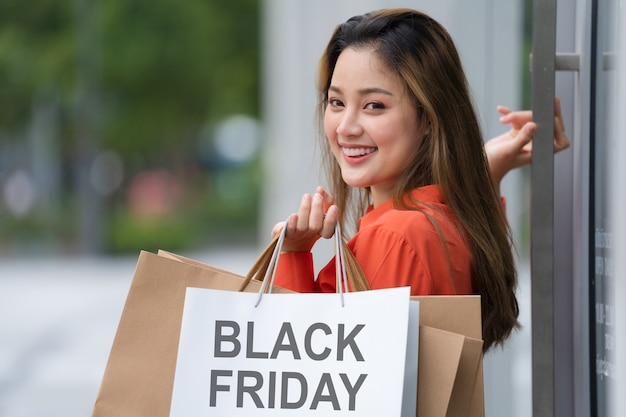 Концепция черной пятницы, женщина, держащая много сумок, гуляет с красочными сумками возле магазина во время процесса покупок