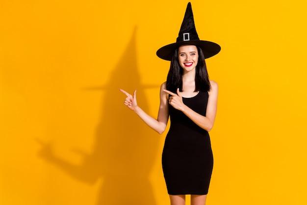 ブラックフライデー割引。かわいい魅力的な若い魔術師の女性マジシャン直接指空のスペース光沢のある笑顔の写真は、明るい黄色の背景を分離した黒い帽子のドレスを着用します