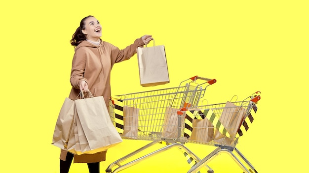 Black friday, a happy girl with shopping in her hands is standing at the shopping cart