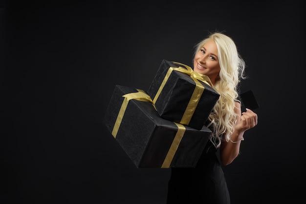 Праздник черной пятницы. блондинка женщина, держащая кредитную карту на темной стене. подарочные коробки