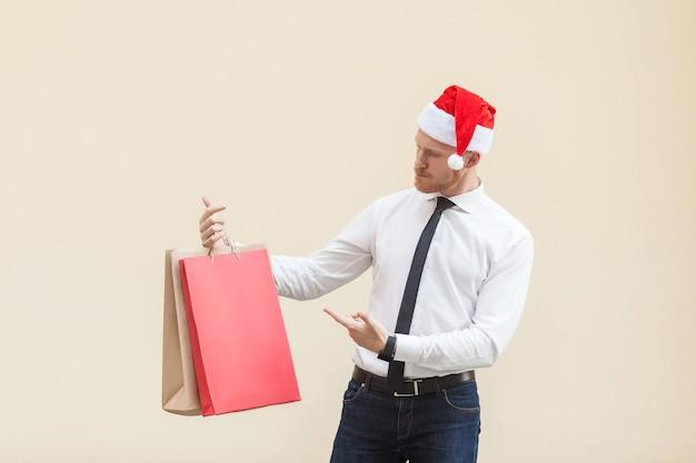 겨울의 블랙프라이데이. 산타 모자를 쓴 행복 빨간 머리 사업가, 손에 쇼핑백을 들고, 손가락을 가리키고, 선물을 보고 있습니다. 실내 촬영, 밝은 주황색 배경