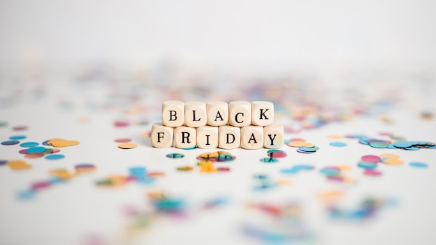 Black friday inscription on small white cubes with confetti