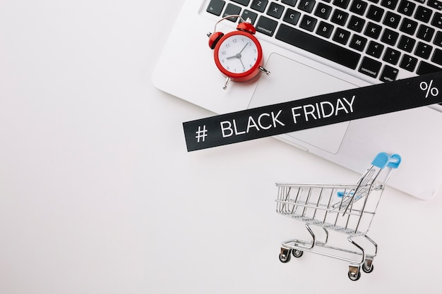 Black friday laptop with clock and shopping cart with copy space