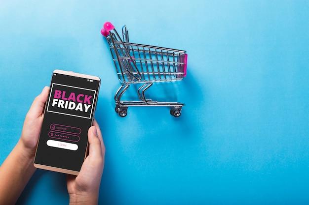 Черная пятница сообщение на смартфоне и корзине на светло-синем фоне.
