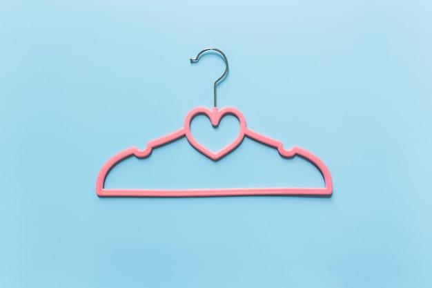 검은 금요일 또는 파란색 배경에 의류 산업 개념은 옷걸이에 심장 모양의 단일 분홍색 옷 걸이로 누워