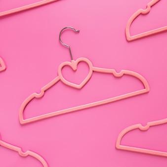 분홍색 배경에 검은 금요일 또는 의류 산업 개념은 옷걸이에 심장 모양으로 무작위로 흩어져있는 분홍색 옷을 옷걸이 패턴으로 누워