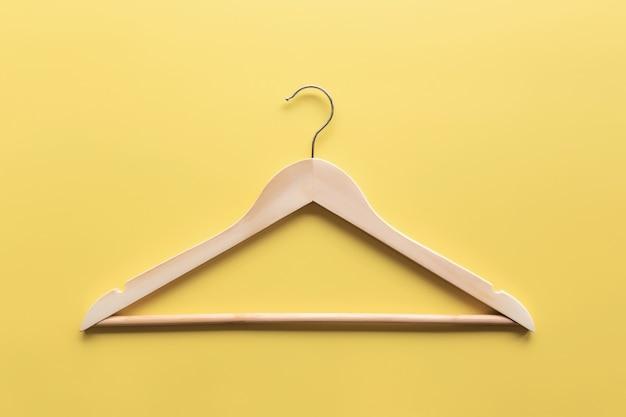 검은 금요일 또는 노란색 배경 평면에 의류 산업 개념은 하나의 고립 된 나무 옷걸이와 함께 누워