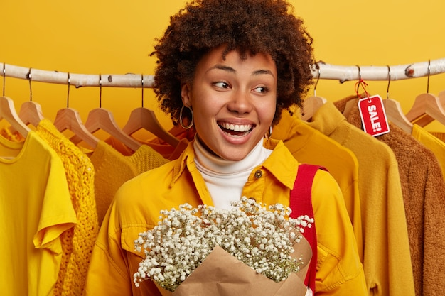 Black friday and price reduction concept. positive curly woman rejoices shop fifty percent off offer, can buy many outfits for not much money, stands near showcase with yellow clothes, carries flowers