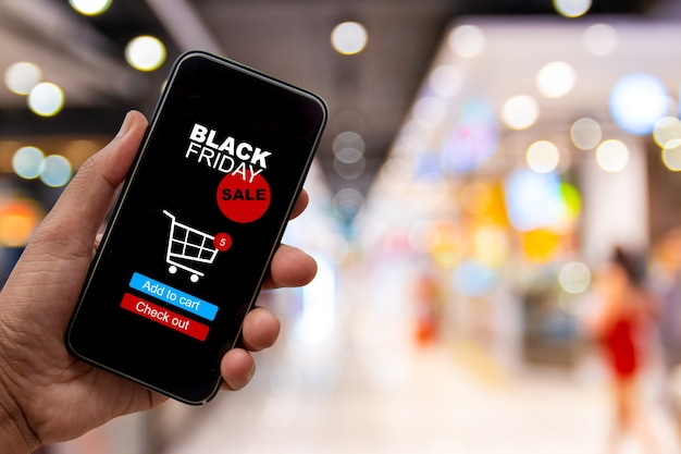 Black friday sale banner, hands are shopping with smartphones during black friday sale