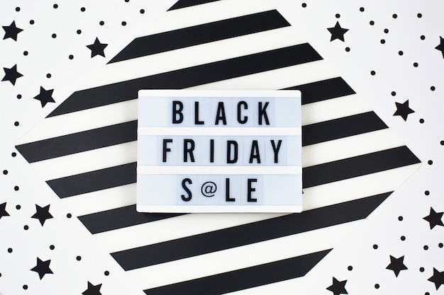 Black friday sale banner text on white lightbox and black stars around