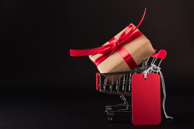 Black friday sale concept gift box wrapped brown paper in the shopping cart and red tag label