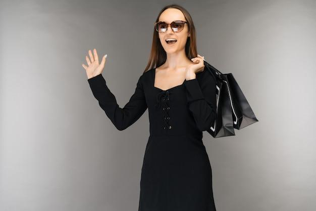 검은 금요일 판매 개념. 휴일에 배경에 고립 된 가방을 들고 충격 된 여자