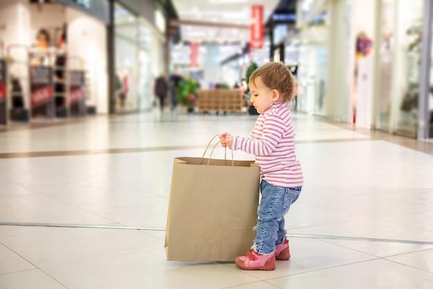 블랙 프라이데이 판매 개념, 아이들과 함께 쇼핑, 자연 친화적인 쇼핑. 작고 귀여운 여자 아이는 카피스페이스로 쇼핑하기 위해 큰 공예 종이 가방을 집어듭니다. 클로즈업, 소프트 포커스, 백그라운드에서 쇼