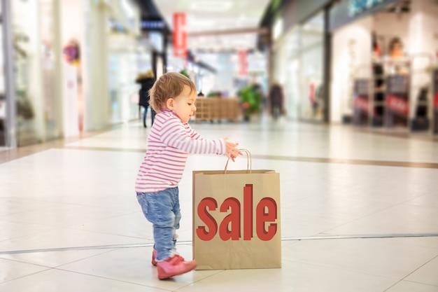 블랙 프라이데이 판매 개념, 아이들과 함께 쇼핑, 자연 친화적인 쇼핑. 작고 귀여운 소녀는 비문 판매로 쇼핑하기 위해 큰 공예 종이 가방을 가져갑니다. 클로즈업, 소프트 포커스, 백그라운드에서
