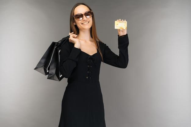검은 금요일 판매 개념. 휴일에 배경에 가방과 신용 카드를 들고 쇼핑 여자