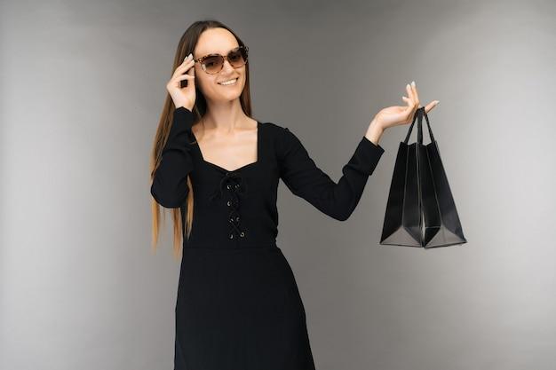 검은 금요일 판매 개념. 휴일에 배경에 고립 된 가방을 들고 쇼핑 여자-이미지