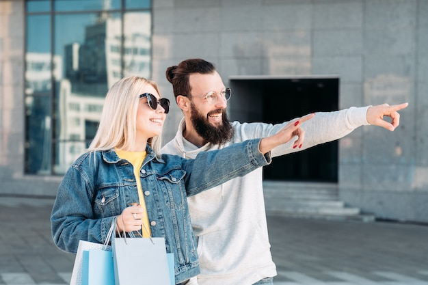 Black friday sale excited couple with paper bags pointing at virtual object