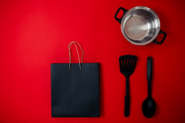 Black friday sale flat lay, banner for home goods shop, silver saucepan, spatula, big spoon on the red surface,