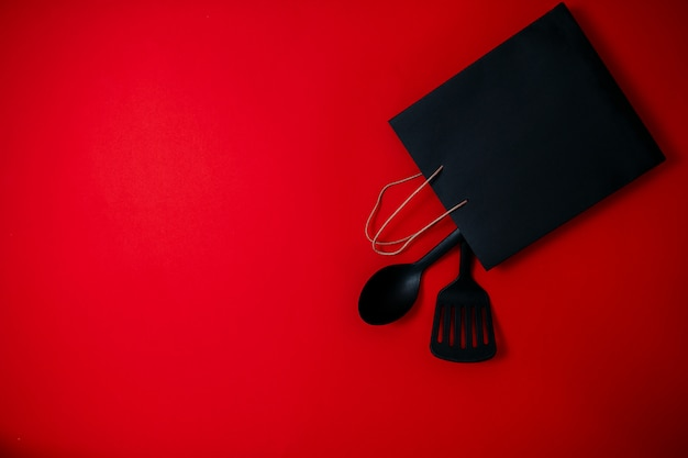 Black friday sale flat lay, banner for home goods shop, spatula, big spoon and black bag on the red surface,