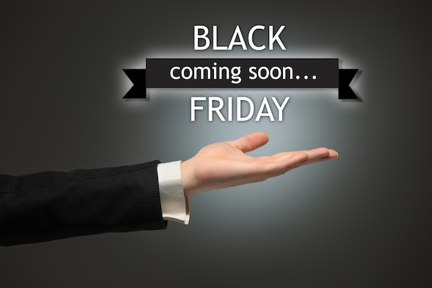 Black friday sale - holiday shopping concept - text and male hand on black