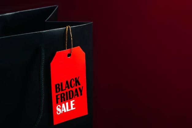 黒い紙袋の濃い赤の背景にブラックフライデーセールラベル