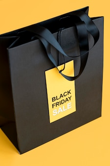 Black friday sale label and shopping bag high view