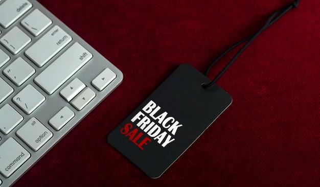 濃い赤の背景にコンピューターのキーボードとブラックフライデーセールラベル