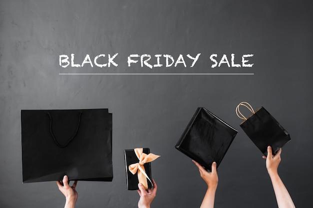 ブラックフライデーセールまたはショッピングバッグやギフトを手で持ち上げるオンラインショッピングプロモーションのコンセプト