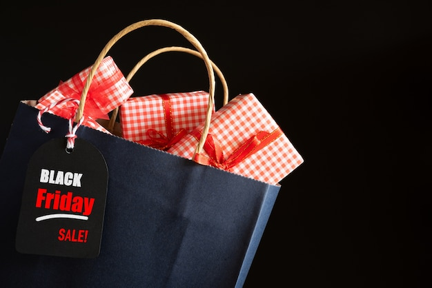 메시지 태그와 함께 검은 금요일 판매 쇼핑 가방 및 선물 상자. 쇼핑 개념