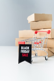 Black friday sale shopping cart in front of boxes