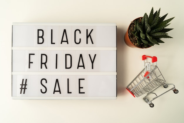 Black friday sale text on light board with plant