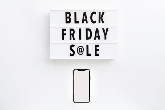 Black friday sale text on lightbox and mobile phone on white background