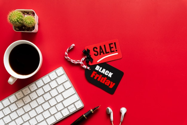 Black friday sale text on a red and black tag with coffee cup, keyboard on red background