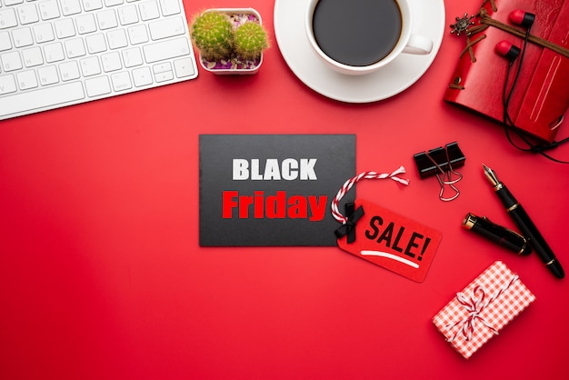 Black friday sale text on a red and black tag with coffee cup on red background. shopping