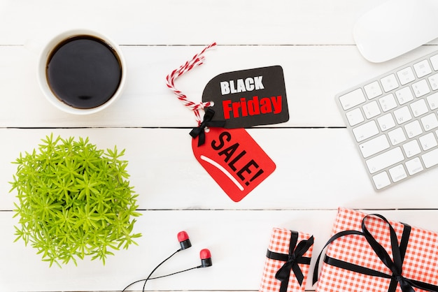 Black friday sale text on a red and black tag with coffee cup on white table background