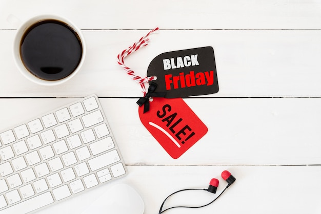 Black friday sale text on a red and black tag with coffee cup on white wooden background.