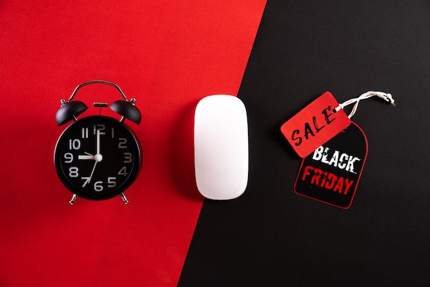 Black friday sale text with alarm clock, white mouse on red black background.