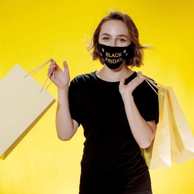 ブラックフライデーセール。ブラックフライデーの買い物袋を手にしたフェイスマスクの女性。パンデミック時の販売。