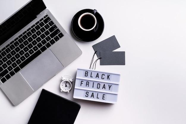 Черная пятница распродажа слова на лайтбоксе с чашкой кофе, ноутбуком и часами