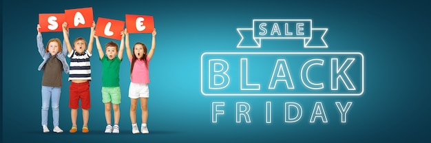 Black friday, sales concept. group of childrens, kids and teens in bright clothing with emotions of happiness holdind letters on blue gradient background. neon words. negative space for your ad.