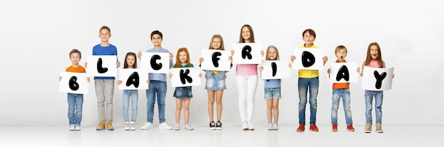 Black friday, sales concept. group of childrens, kids and teens in bright clothing with emotions of happiness holdind letters on white background. negative space. colorful image for your ad.