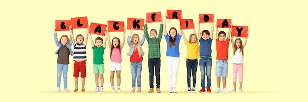 Black friday, sales concept. group of childrens, kids and teens in bright clothing with emotions of happiness holdind letters on yellow background. negative space. colorful image for your ad.