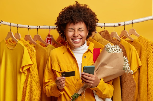 Black friday and sales concept. overjoyed dark skinned woman has curly hair, smiles broadly, holds bouquet