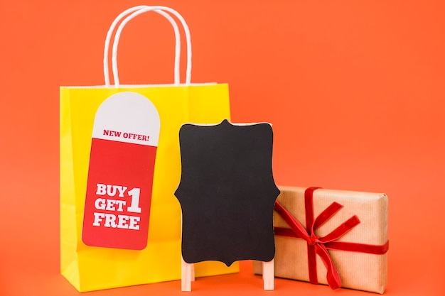 Black friday sales concept with bag and gift box behind board