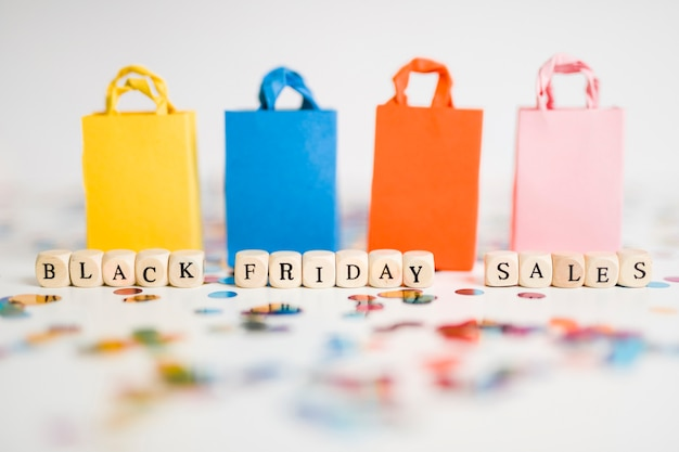 Black friday sales inscription on cubes with colourful shopping bags