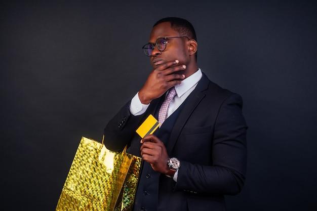 블랙프라이데이 쇼핑 . 스튜디오의 검정색 배경에 구매 및 신용 카드가 든 패키지 가방을 들고 있는 아프리카계 미국인 사업가