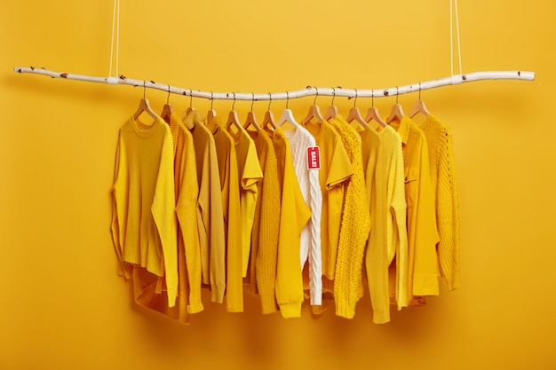 ブラックフライデー、ショッピング、大きな販売コンセプト。衣料品店のラックにラベルタグがぶら下がっている黄色い服と白いセーターの詳細画像。